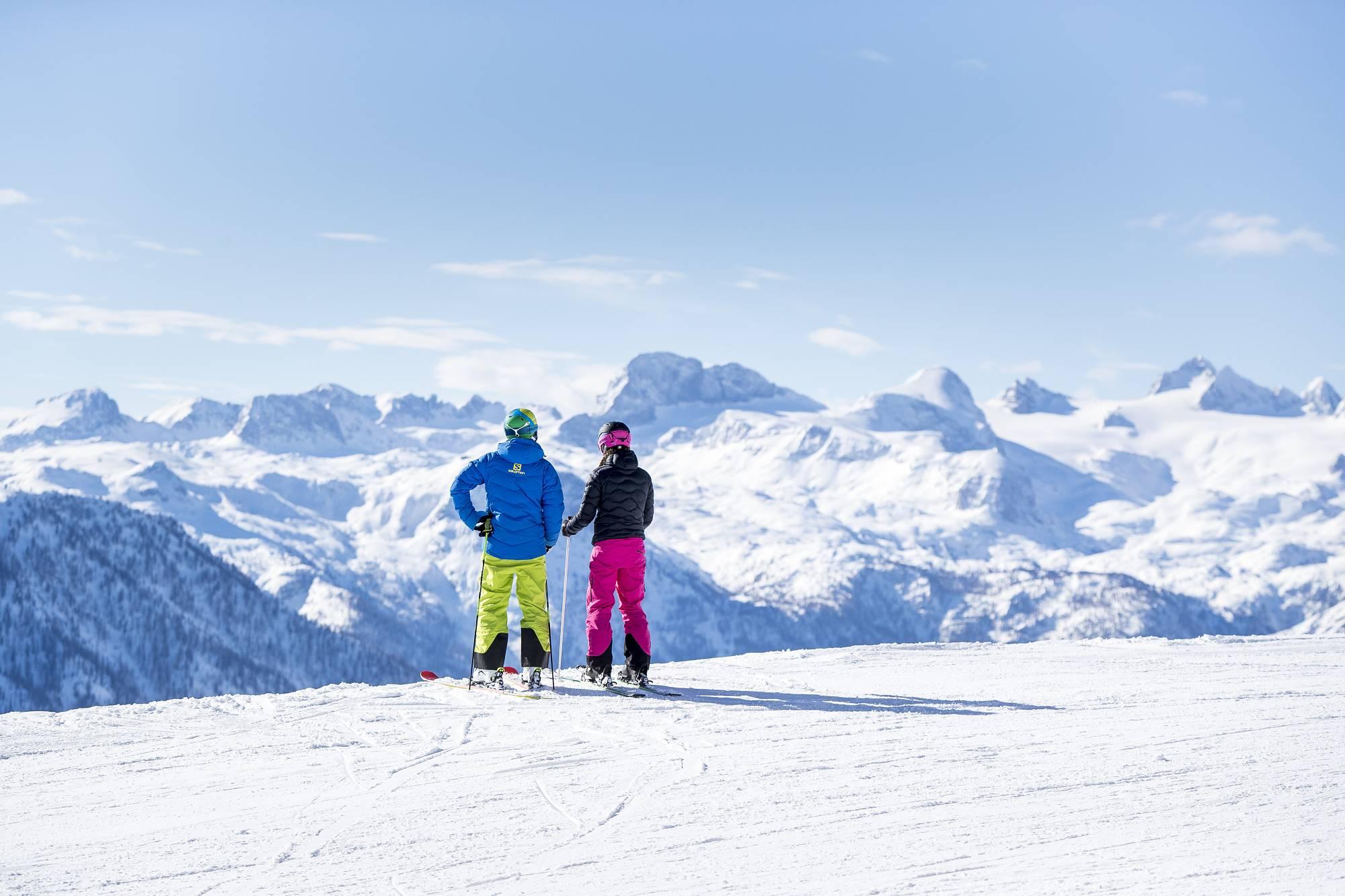 Zwei Skier auf der sicheren Piste vor dem Dachstein Gletscher Panorama.