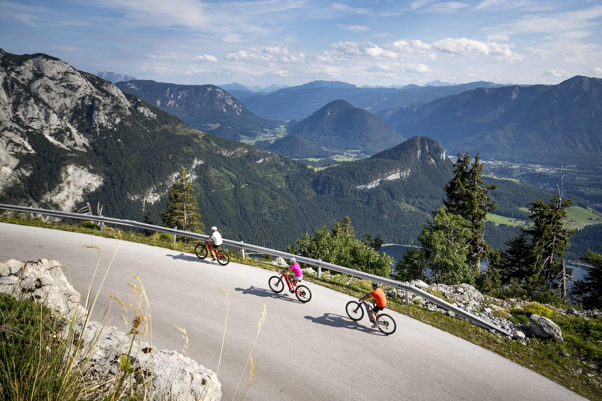 Drei Fahrradfahrer radeln sportlich die Loser Panoramastrasse bergauf.