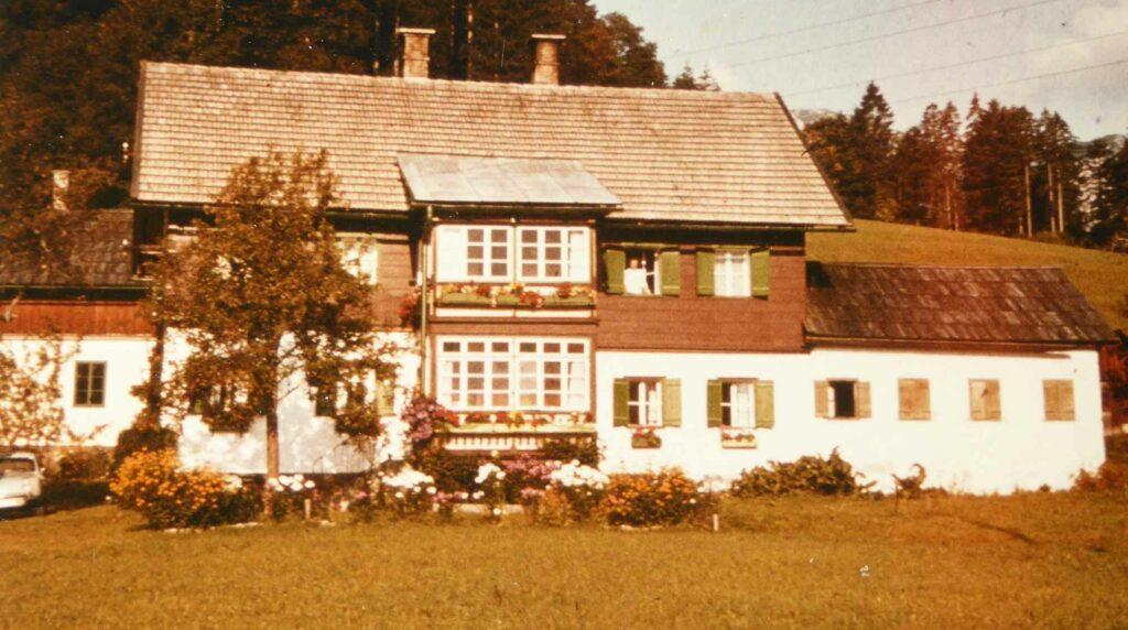 Eine alte Aufnahme des Gästehauses Starl mit Blumen im Garten.